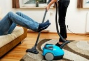 Image of women hoovering while man relaxes
